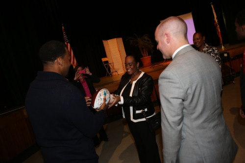 GGLA teacher, Ms. Lakisha Clark accepts a signed Miami Dolphins football from R.J. Stanford. (Photo credit: UPS)